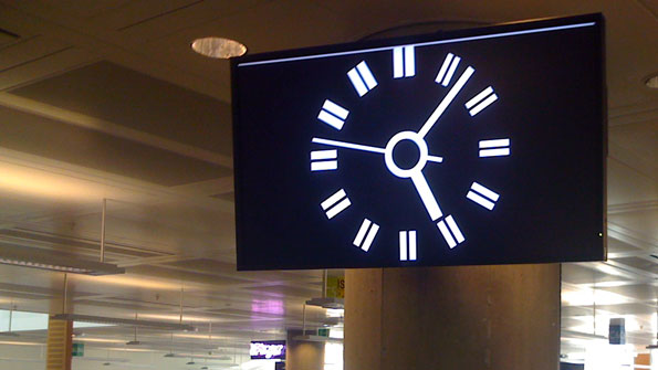 1980s style BBC2 clock, on a widescreen monitor, high on a pillar, in an open plan office