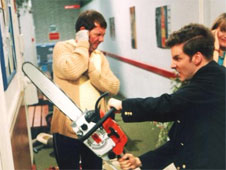 Still from the sitcom 'The Brittas Empire'. Gordon Brittas wields a chainsaw in the corridor of the leisure centre. Two of his members of staff look on.