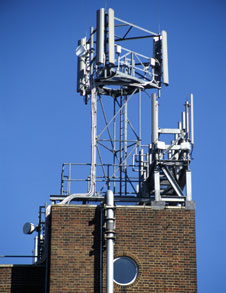 A picture showing a mobile phone mast on a brick bulding