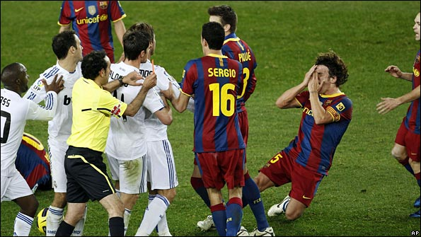 Carles Puyol goes to ground after being pushed in the face by Sergio Ramos