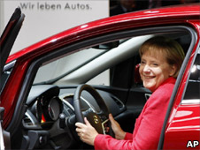German Chancellor Angela Merkel sits in an Opel Astra car at the IAA Frankfurt Auto Show in Frankfurt, Germany, 17 Sept 2009. Slogan translates 'We live cars'