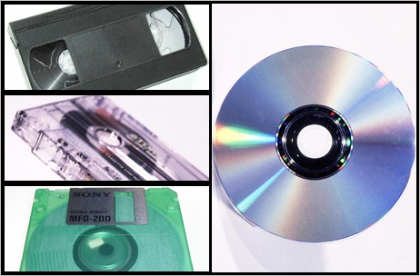 A video cassette (top left) audio cassette (centre left) and floppy disc (bottom left) and a CD (right)