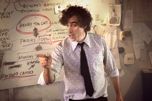 Stephen Mangan as Dirk Gently surrounded by a wall of paper notes.