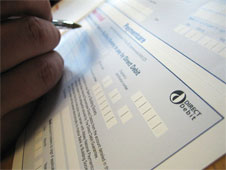 Close up of someone filling out a direct debit form to pay bills