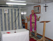 Chaplain Andrew Martlew in his chapel.  The room is small and the furniture seems almost makeshift, with benches, a rug on the floor, a crucifix on the wall and a curtain behind the small altar to divide the room in two