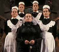 an old woman in black victorian clothing surrounded by four young women in black and white maidservant outfits