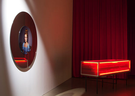 Miriam Bäckström, Attractions/Red Vitrine (2010). Coloured (red) vitrine in glass and wood, with interior made of wood and coloured mirrors, neon light (red) with electric support. Four black painted iron legs. Objects placed in the interior, on the mirrors.