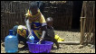 Woman washes up in a plastic bowl in Daaba village Kenya