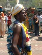 Man in colourful garlands, with tiny silvery pots hooked into his skin
