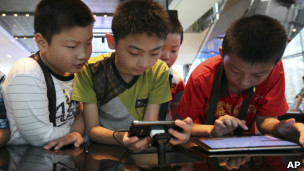 Kids looking at smartphones and tablet computers in Seoul, South Korea