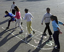 Children playing hopscotch in playground