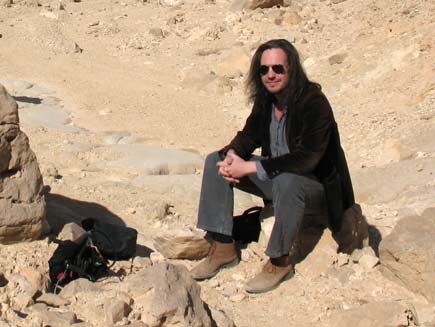 Nicholas Buxton, a long-haired man wearing sunglasses and dust-covered walking shoes, sits on a stone in the sun in the Egyptian desert