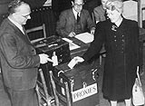 Photo of a woman who is voting by proxy for her husband who is stationed overseas, during the 1945 General Election