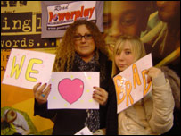 Mother and daughter with 'I Love Brad' posters