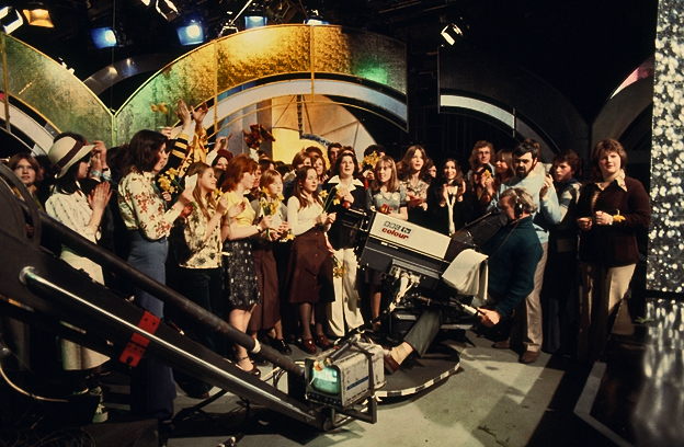 A camera films audience members in the Top of the Pops studio.