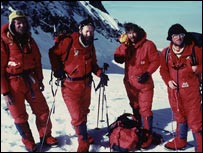 Four climbers in all-in-one red suits.