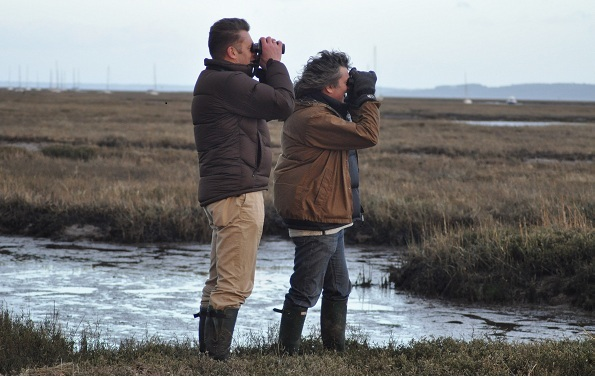 Chris Packham and Martin Hughes-Games looking through binoculars