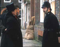 a man dressed in old style police uniform talking to two men