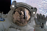 Japanese astronaut Soichi Noguchi waves at a crewmate during a spacewalk.The Earth is in the background