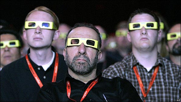 Spectators watch a large screen in 3-D spectacles