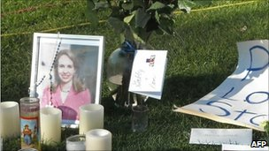 Photographs of US Congresswoman Gabrielle Giffords are set amid flowers and candles outside the University Medical Center in Tucson, Arizona