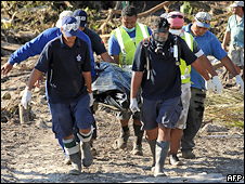 Rescue workers recover the body of a woman from the debris of tsunami devastated Lalomanu in Samoa on October 1, 2009