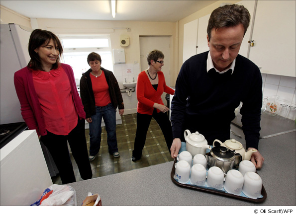 David Cameron is watched by his wife Samantha during their visit to a parenting resource centre in Halifax