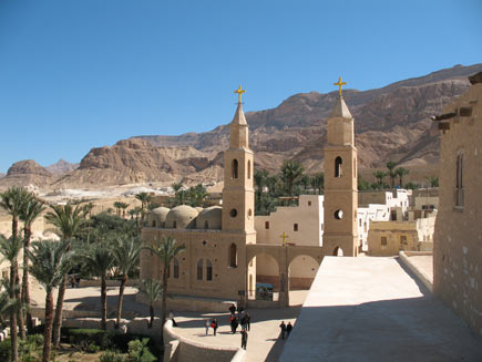 Saint Antony's monastery, a collection of warm-coloured stone buildings with small, arched windows.  Two steeples topped by Christian crosses stand either side of the double arch entrance.  Palm trees grow in small walled patches of green space outside the walls