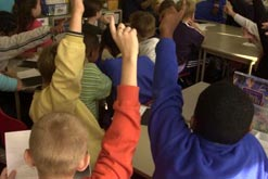 Picture shows pupils with arms raised in a school classroom
