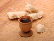 Broken loaf of bread and wine in a wooden cup