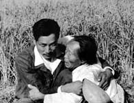 Korean civilians huddled together in a field