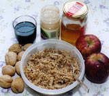 Bowl of charoset paste with ingredients: walnuts, wine, cinnamon, honey and apples