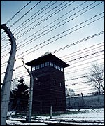 A watchtower through the barbed wire at Auschwitz
