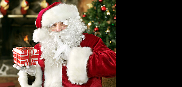 father christmas holding a christmas present - Christmas In Wales