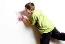 a boy drawing on the wall, istock image