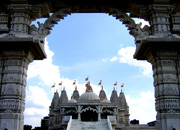Swaminarayan Hindu temple seen from an ornately arched gateway