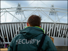 A security guard stands out side the Olympic Stadium at Olympic Park in Stratford, London, England