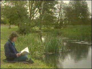 Penny Hemphill reading on the river bank