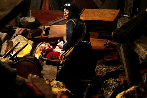 Kay, played by Anna Maxwell-Martin, stands over Helen, played by Claire Foy, lying in the rubble.