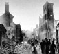 Photo of Coventry, after the air raid of 14 November 1940. People walk through the ruins of their city.