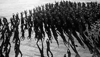 While en route to Africa to take part in Operation Torch (the Allied landings in Morocco), enlisted men do their jumping jacks on the flight deck of the aircraft carrier USS 'Santee'