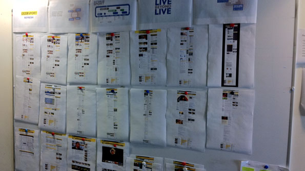 Picture of printouts of site designs, on a whiteboard, on a wall.