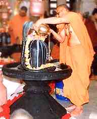 A Hindu monk in orange robes pours water over the phallic symbol of Shiva