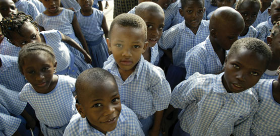 A large group of young schoolchildren faces the camera. They are wearing in blue and white checked uniform shirts and dresses.