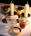 Wine cup, candles and wafers for the ceremony of the Eucharist