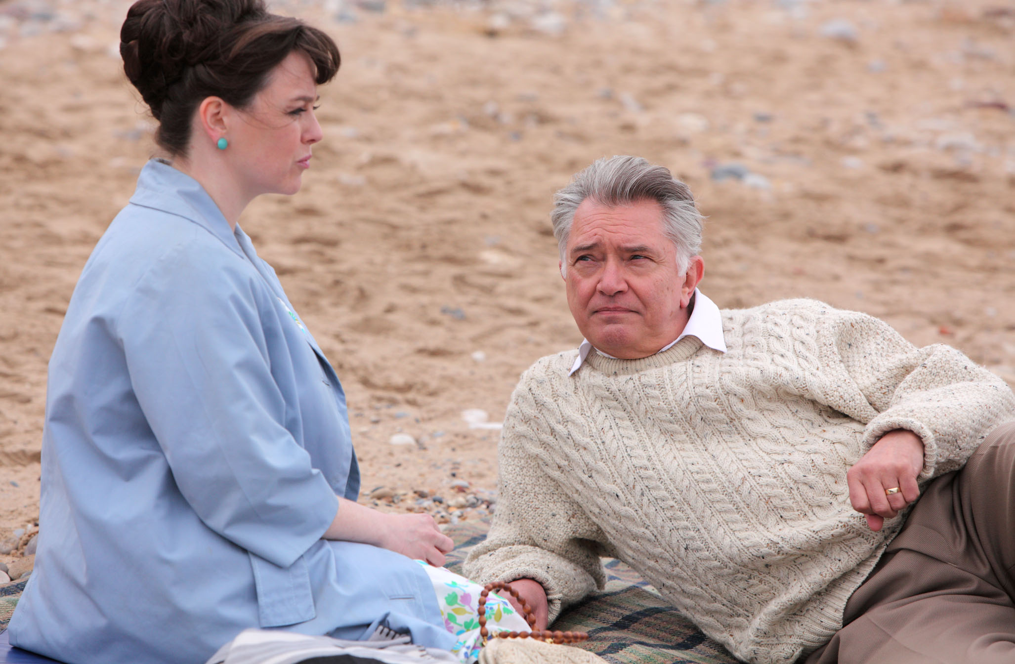 Inspector George Gently, played by Martin Shaw, sits on the beach with Lisa Bacchus, played by Marie Clare Pullen
