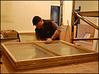 A carpenter working on one of the windows