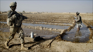 US soldier passes by an Afghan farmer