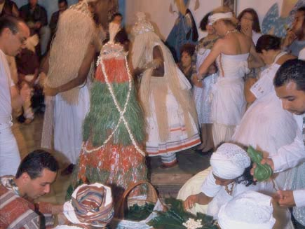Crowd of people in a room. Foreground shows people on the floor preparing food in leaves. Main background shows man, dressed in white, standing up with rafia fringe covering his face, dancing.
