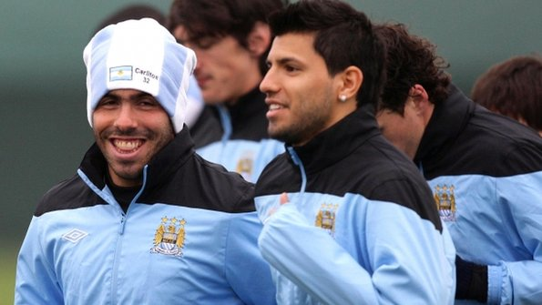 Carlos Tevez in training with team-mate Sergio Aguero (right)